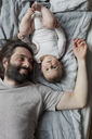 Directly above shot of father and baby girl lying in bed - FSIF00040