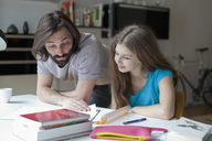 Father assisting daughter in doing homework at table - FSIF00046