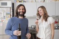 Happy couple enjoying red wine in kitchen - FSIF00049