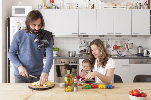 Father chopping vegetables with mother and baby girl playing in kitchen - FSIF00070