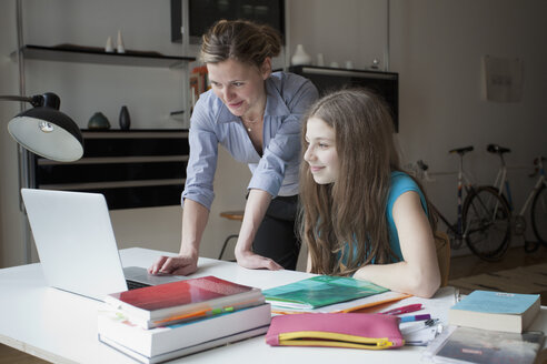 Mother and daughter using laptop at study table - FSIF00079