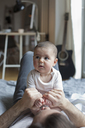 Cute baby girl sitting on father at home - FSIF00082