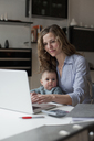 Woman working on laptop while sitting with baby girl at home - FSIF00094