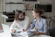 Mid adult couple looking at each other while working at home - FSIF00112