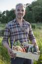 Portrait of confident mature man carrying crate of freshly harvested vegetables at garden - FSIF00184