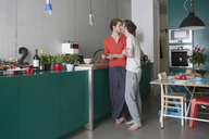 Full length of romantic gay couple kissing in kitchen - FSIF00199