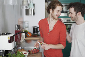Affectionate gay couple looking at each other in kitchen - FSIF00217