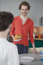 Smiling gay man holding croissants in plate looking at partner at home - FSIF00220