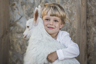 Boy holding baby goat against wall - FSIF00241