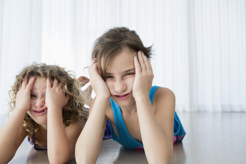 Portrait of frustrated sisters with head in hands lying on floor at home - FSIF00244