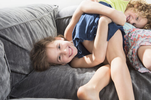 Portrait of sisters playing on sofa in house - FSIF00247