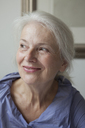 Close-up of smiling senior woman looking away at home - FSIF00265