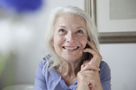 Happy senior woman looking up while answering mobile phone at home - FSIF00268
