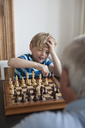 Little boy playing chess with grandfather at home - FSIF00271