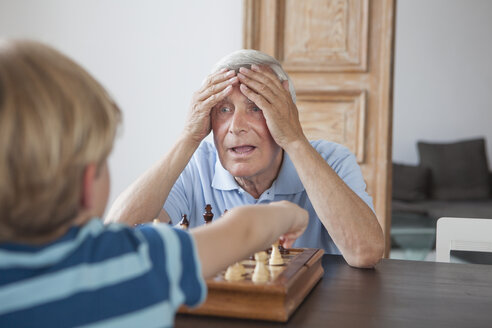 Shocked senior man with head in hands looking at grandson while playing chess at home - FSIF00274