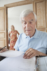 Senior man examining financial documents with woman in background at home - FSIF00277