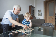 Grandfather solving jigsaw puzzle with grandson in living room at home - FSIF00280