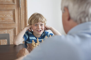Happy grandson playing chess with grandfather at home - FSIF00283