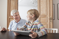 Happy senior man looking at grandson with digital tablet at home - FSIF00286