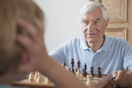 Senior man playing chess with grandson at home - FSIF00289