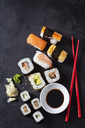 Variety of sushi with wasabi, ginger and bowl of soy sauce on dark ground - CSF28916
