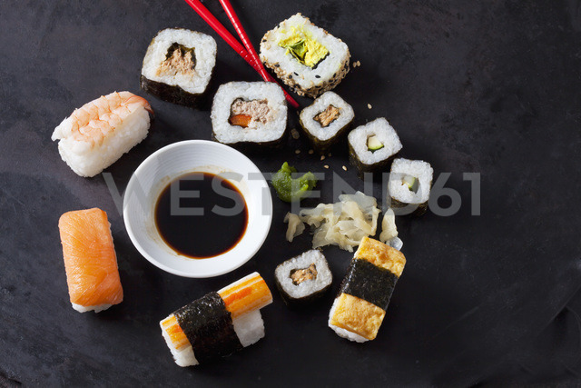 Variety of sushi with wasabi, ginger and bowl of soy sauce on dark ground - CSF28919
