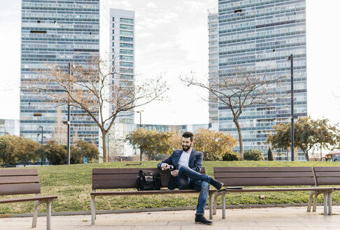 Businessman sitting on bench outside office building drinking coffee - JRFF01539
