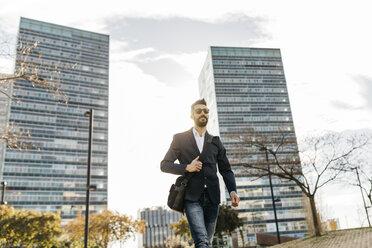 Businessman wearing sunglasses walking outside office building - JRFF01542