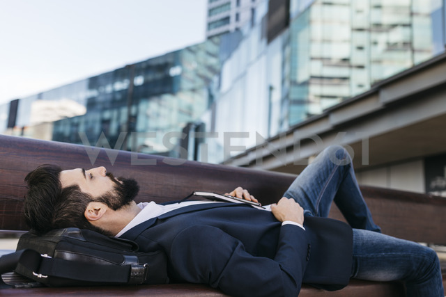 Businessman lying on bench outside office building - JRFF01545