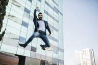 Businessman jumping outside office building - JRFF01548