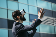 Businessman using virtual reality glasses outside office building - JRFF01551