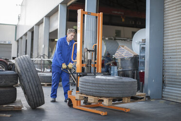 Worker moving a tire using a mobile forklift - ZEF14953