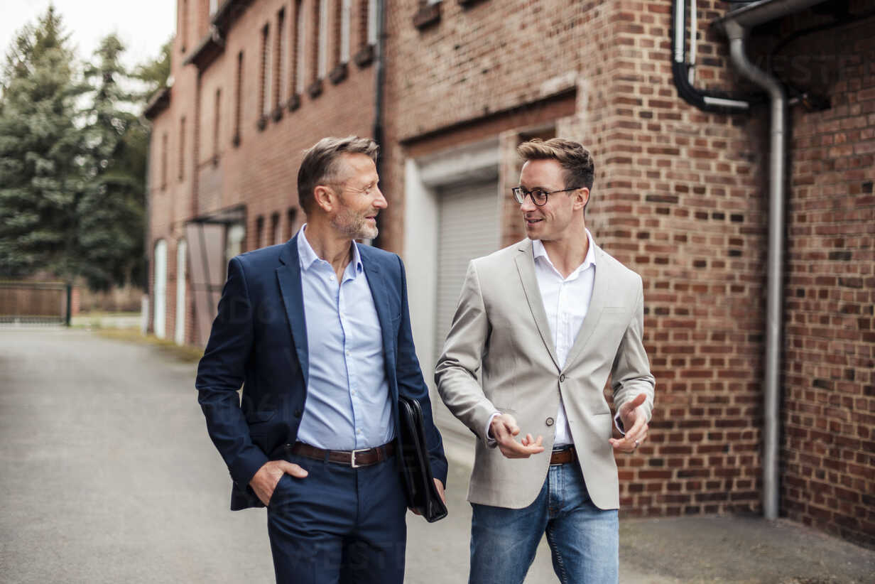 Two businessmen talking at brick building - DIGF03305 - Daniel Ingold/Westend61