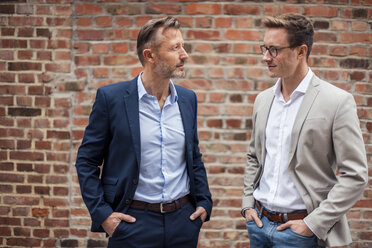 Two businessmen standing at brick building - DIGF03308