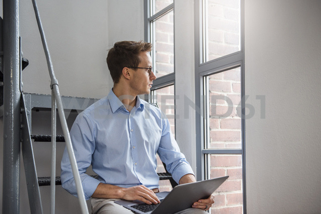 Young businessman using laptop on stairs - DIGF03317