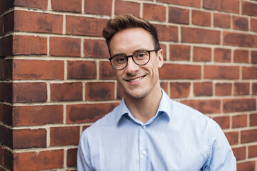 Portrait of smiling young businessman at brick wall - DIGF03326