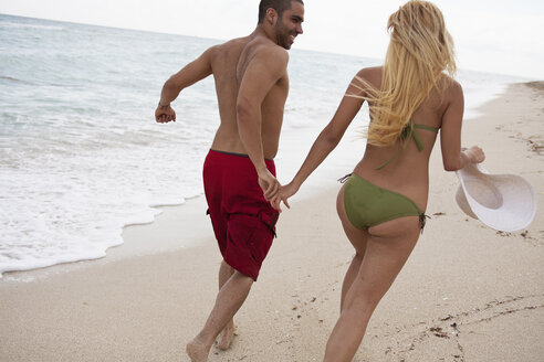 A young couple holding hands and running on the beach - FSIF00355