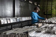 A young man searching through records in a record store - FSIF00361