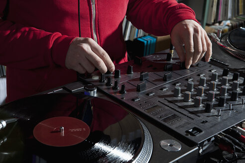 A DJ adjusting knobs on a sounder mixer, detail of hands - FSIF00373