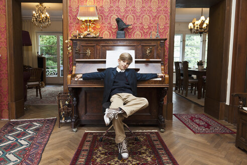 A boy with a cool attitude posing at an old-fashioned upright piano - FSIF00379