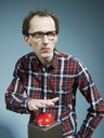 A nerdy guy with his hand poised above a red game show buzzer - FSIF00388