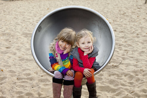 Two girls sitting on spherical metal chair in park - FSIF00415