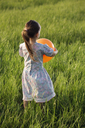 Rear view of a girl holding a balloon in a field - FSIF00448