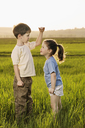 A boy and a girl in a field comparing heights - FSIF00454