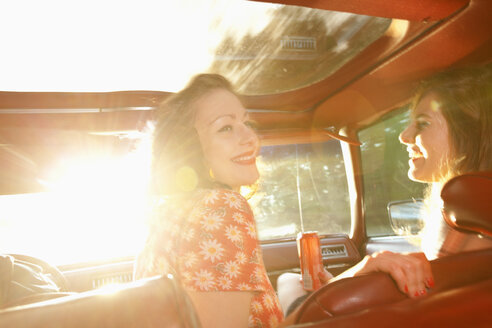 Two rockabilly women having fun in the front seat of a vintage car - FSIF00487