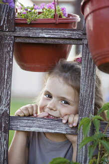 A young smiling girl looking through a trellis - FSIF00520