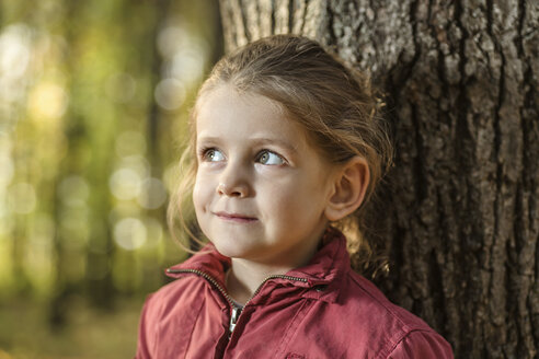 A young girl looking away curiously while leaning against a tree trunk - FSIF00523
