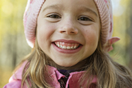 A cheerful young girl wearing a pink knit hat and grinning - FSIF00538