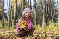 A cheerful girl picking up autumn leaves in a wooded area - FSIF00544