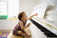 A little boy sitting at a piano reaching out with curiosity for the sheet music - FSIF00553